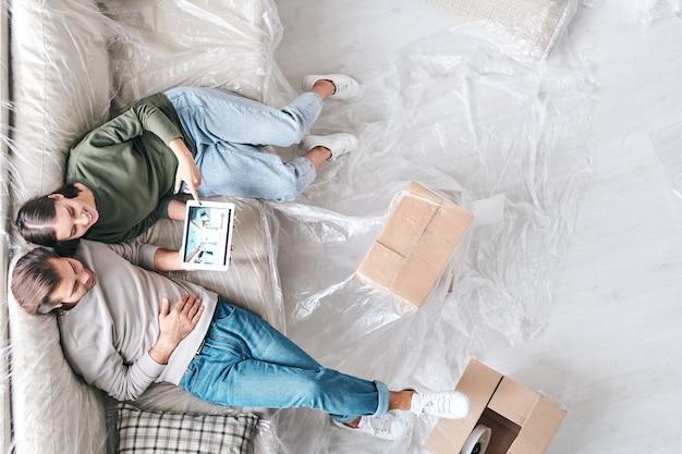 Panoramica di giovane coppia affettuosa con tablet seduto sul nuovo divano e guardando attraverso annunci di interni o vendita di immobili
