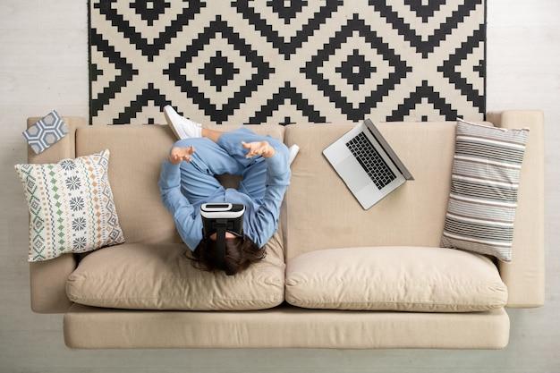 Panoramica della giovane donna bruna in pigiama blu e auricolare vr seduta su un divano morbido con le gambe incrociate e toccando il display virtuale