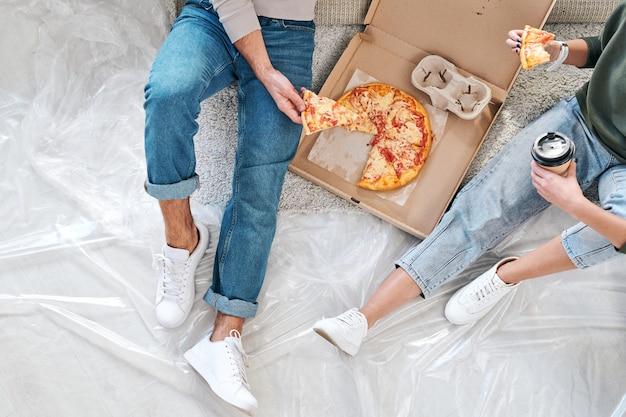 Panoramica della giovane coppia in abbigliamento casual seduto sul pavimento e mangiando pizza dalla scatola e caffè dopo il trasferimento in un nuovo appartamento o casa