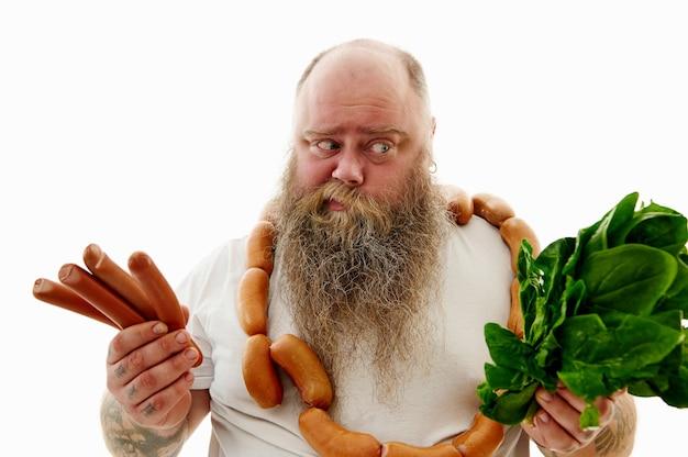 Un uomo in sovrappeso che sceglie ciò che è meglio per la salute: salsicce o verdure. uomo barbuto obeso con un bruch di salsicce intorno al collo.