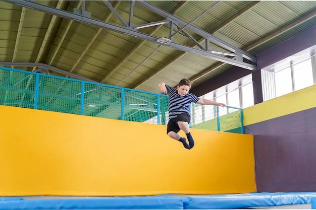 Ragazzino sveglio in sovrappeso che salta sul trampolino al chiuso in un centro sportivo per bambini