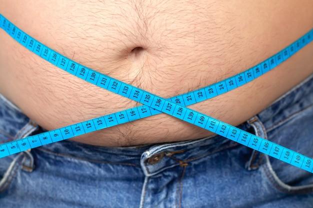 L'uomo in sovrappeso misura la sua pancia grassa