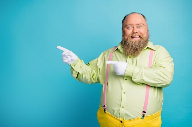 Uomo in sovrappeso punto dito spazio vuoto sfondo blu