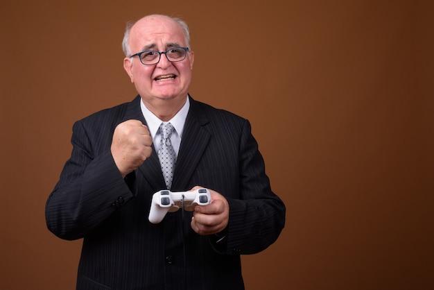 Uomo d'affari senior in sovrappeso che gioca e che tiene il controller di gioco