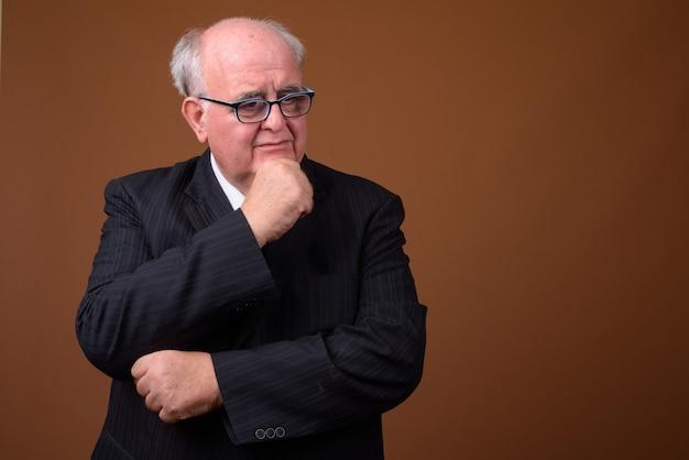 Uomo d'affari senior in sovrappeso che indossa occhiali da vista contro il muro marrone