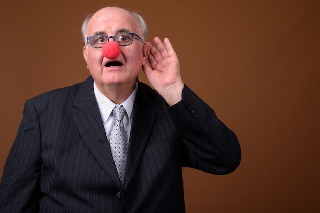 Uomo d'affari maggiore di peso eccessivo che porta il naso rosso del pagliaccio