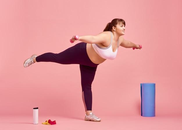 Donna in sovrappeso che fa esercizio di equilibrio, corpo positivo, muro rosa
