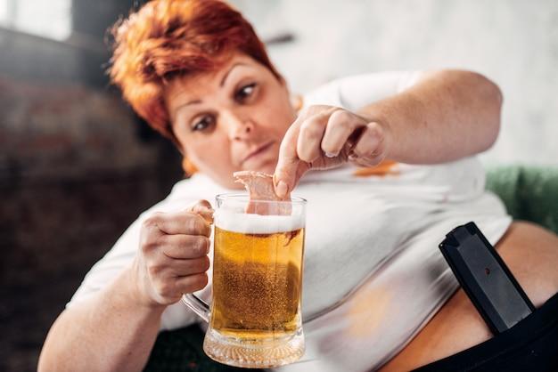 La donna in sovrappeso beve birra, obesità