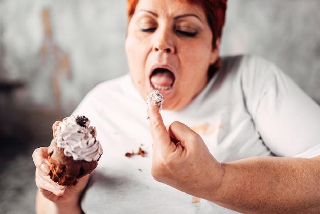 La donna in sovrappeso mangia torta dolce, pigrizia e obesità. cibo malsano mangiare, femmina grassa