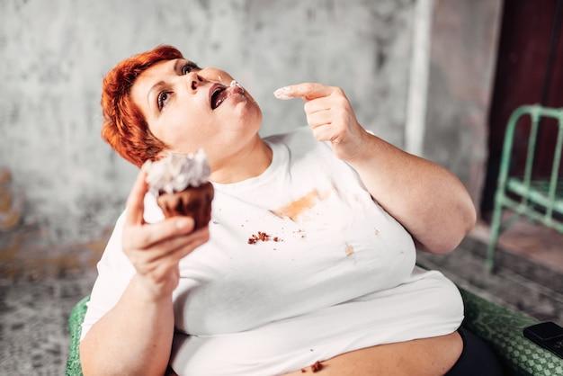 La donna in sovrappeso mangia la torta dolce, l'obesità