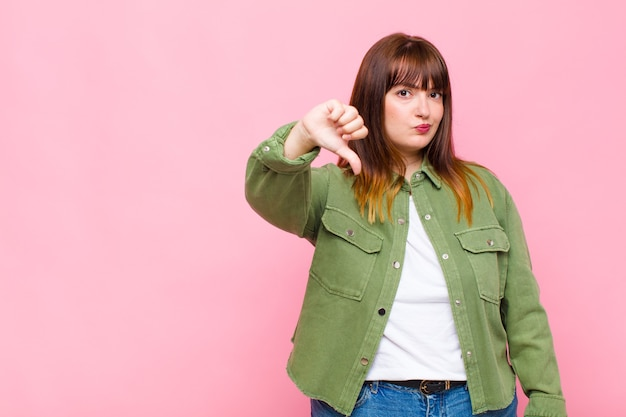 Donna in sovrappeso che si sente arrabbiata, arrabbiata, infastidita, delusa o scontenta, mostrando i pollici verso il basso con uno sguardo serio