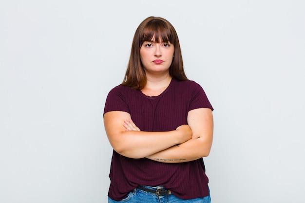 Donna in sovrappeso che si sente scontenta e delusa, sembra seria, infastidita e arrabbiata con le braccia incrociate