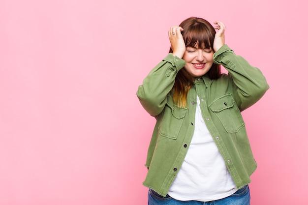 Donna in sovrappeso che si sente stressata e ansiosa, depressa e frustrata con un mal di testa, alzando entrambe le mani alla testa