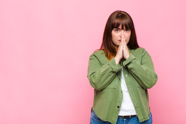 Donna in sovrappeso che si sente preoccupata, piena di speranza e religiosa, che prega fedelmente con i palmi premuti, chiedendo perdono