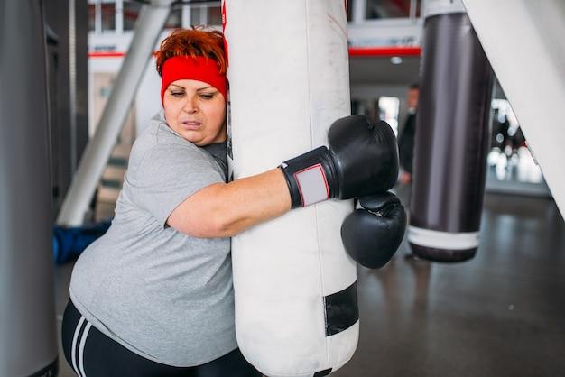 Donna in sovrappeso in guanti, esercizio di boxe con sacco da boxe in palestra.
