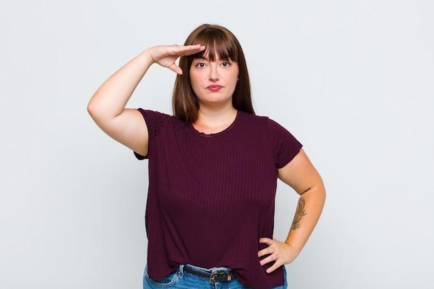 Donna in sovrappeso che saluta la telecamera con un saluto militare in un atto di onore e patriottismo, mostrando rispetto