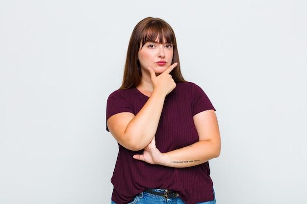 Donna in sovrappeso dall'aspetto serio, premuroso e diffidente, con un braccio incrociato e una mano sul mento, opzioni di ponderazione