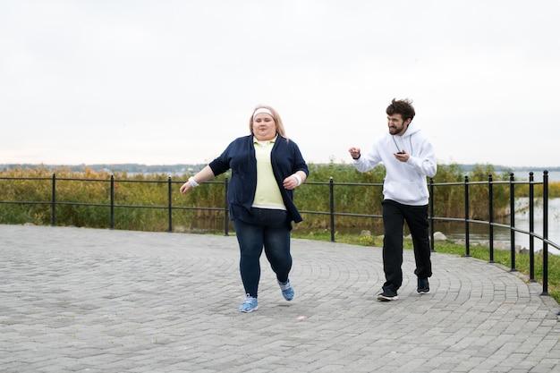 Donna sovrappeso che corre all'aperto