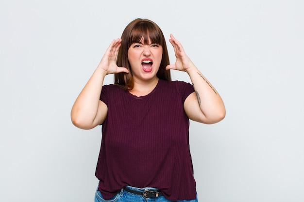Donna in sovrappeso che urla con le mani in alto, sentendosi furiosa, frustrata, stressata e sconvolta