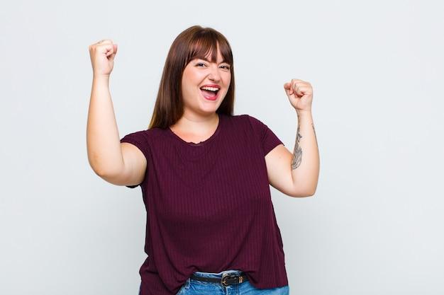Donna in sovrappeso che grida trionfante, guardando come vincitore eccitato, felice e sorpreso, festeggiando