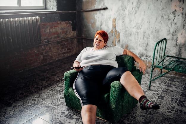 La donna in sovrappeso si siede su una sedia e guarda la tv. stile di vita malsano, obesità
