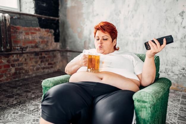 Donna sovrappeso seduta sulla sedia e beve birra, cibo ipercalorico, obesità. stile di vita malsano, femmina grassa