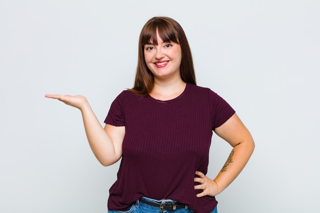 Donna in sovrappeso sorridente, sentendosi sicura, di successo e felice, mostrando il concetto o l'idea sullo spazio della copia sul lato