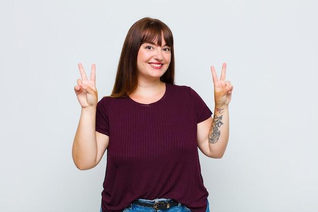 Donna in sovrappeso che sorride e sembra felice, amichevole e soddisfatta, gesticolando vittoria o pace con entrambe le mani
