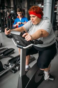 Donna in sovrappeso, allenamento sulla cyclette in palestra. calorie che bruciano, persona di sesso femminile obesa nel club sportivo, persone grasse