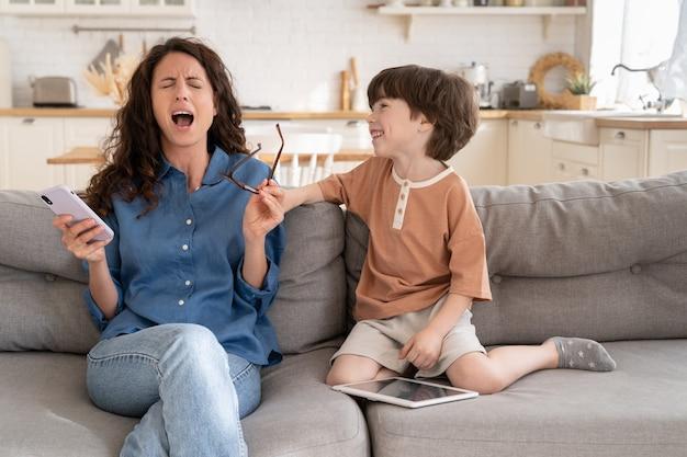 Mamma sopraffatta urla impotente stressata dal figlio prescolare disobbediente che distrae dalla navigazione sul web