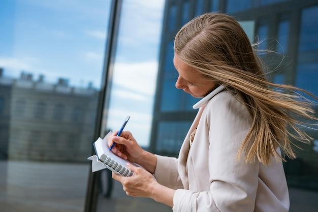 Donna d'affari oberata di lavoro donna d'affari multitasking che parla al cellulare con una giacca leggera ne...