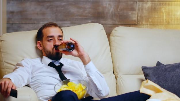 Uomo d'affari oberato di lavoro seduto sul divano usando il telecomando della tv e mangiando patatine a tarda notte.