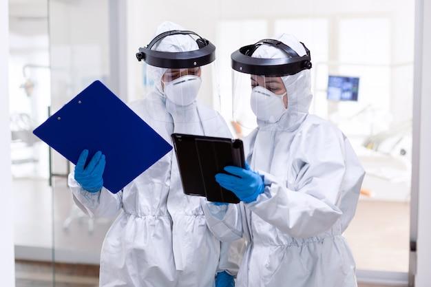 Team di medici oberati di lavoro che lavorano insieme indossando una tuta in dpi in hospita. colleghi medici che indossano indumenti professionali contro l'infezione da coronavirus come precauzione di sicurezza.