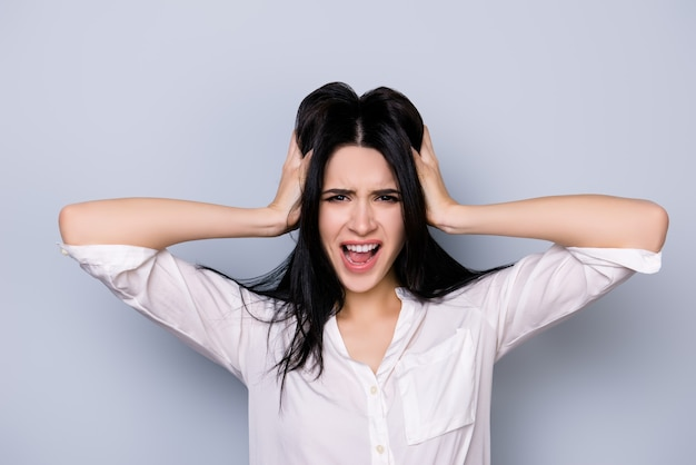 Giovane donna stressata furiosa oberata di lavoro in collera che tocca la testa e urla con la bocca aperta in abbigliamento formale