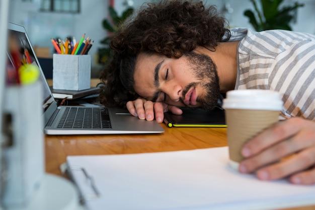 Graphic designer oberato di lavoro che dorme sulla sua scrivania
