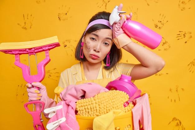 La casalinga oberata di lavoro si sente stanca isolata sopra il muro giallo sporco