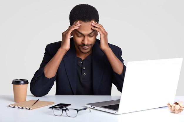 Uomo stressante oberato di lavoro tiene le mani sulla testa, mantiene lo sguardo basso, stanco del costante lavoro al computer portatile
