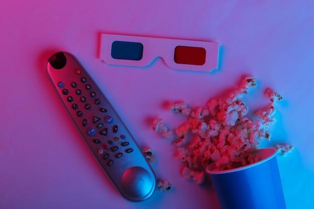 Ovie time secchio di cartone di popcorn tv remoto e carta monouso stereoscopica anaglifi occhiali 3d in luce al neon sfumata blu rosa vista dall'alto