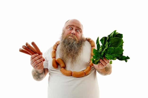 Un pesatore con salsicce al collo ha difficoltà a scegliere il cibo: salsicce o spinaci. ritratto isolato su sfondo bianco