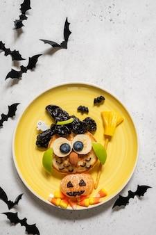 Frittella di gufo con frutta per bambini colazione su halloween
