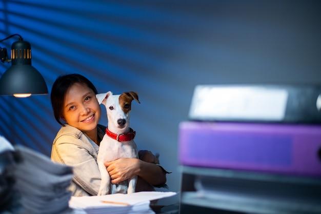 Proprietario e cane che lavorano insieme in ufficio a casa. donna libera professionista abbraccia il suo jack russell terrier e lavora insieme da casa. occupazione amichevole con gli straordinari. ragazza casual asiatica felice del suo lavoro.