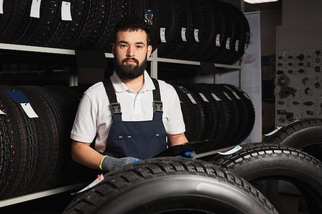 Negozio di garage proprietario che tiene il miglior pneumatico in un supermercato, misurando la ruota di un'auto in gomma. sul posto di lavoro
