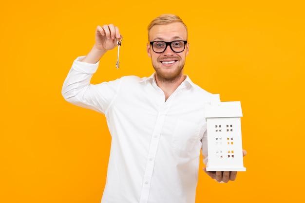 Il proprietario della proprietà detiene un modello di casa e le chiavi in mano su un giallo con spazio di copia