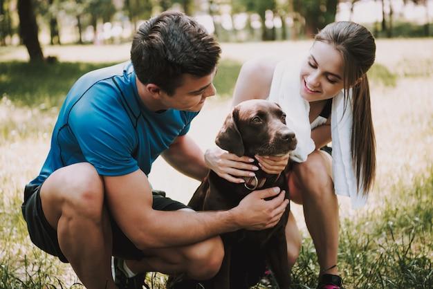 I proprietari sono sorridenti e accarezzano il loro animale domestico a green park