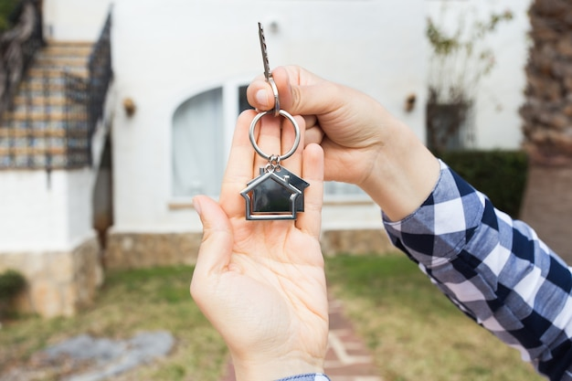 Concetto di proprietà, proprietà e inquilino: chiave in mano femminile per nuova casa e proprietà immobiliare
