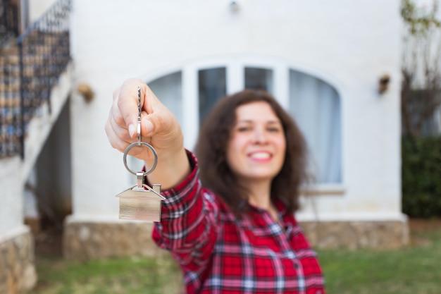 Proprietà, proprietà immobiliare, acquisto e concetto di affitto - donna con le chiavi in piedi fuori dalla nuova casa