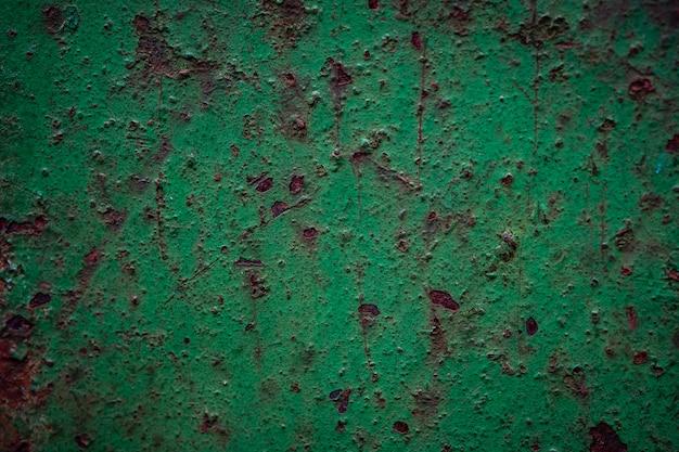 Parete di metallo verde arrugginito ossidato con corrosione e graffi, struttura del vecchio acciaio