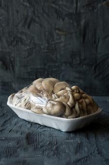 Fungo di ostrica in un pacchetto su fondo di legno scuro