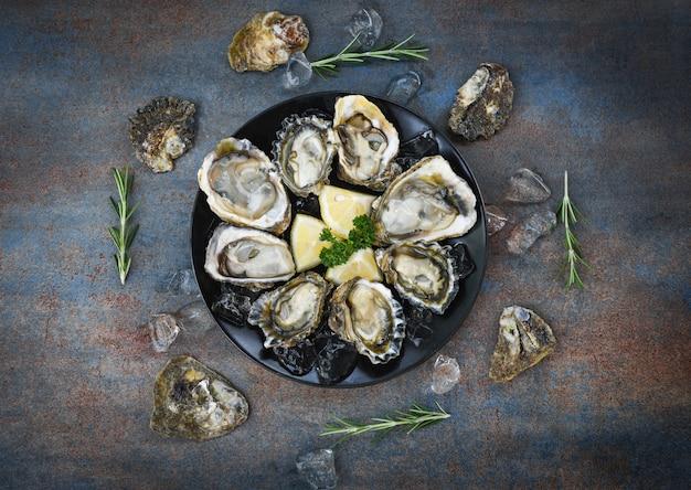 Conchiglia di ostriche con spezie alle erbe limone rosmarino servito da tavola e ghiaccio sano frutti di mare cena di ostriche cruda nel ristorante cibo gourmet / ostriche fresche frutti di mare su piastra sfondo nero