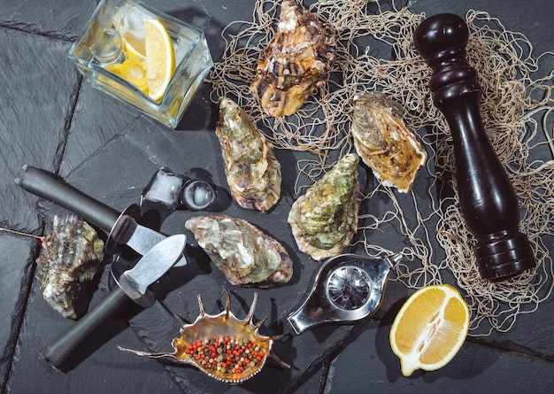 Ostriche su lastra di pietra con ghiaccio, limone, rete da pesca, pepe e coltello.
